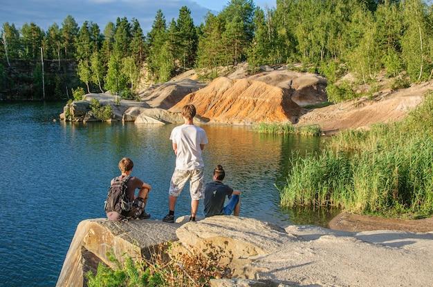 Трое друзей сидят на скале над красивым глубоким гранитным карьером.