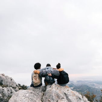 Three friends sitting on the top of mountain enjoying the view