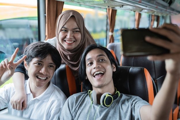 Three friends smile and pose in front of their cellphone camera while taking selfies together on the bus