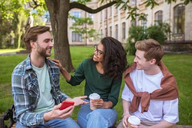 Трое друзей проводят время в парке и разговаривают