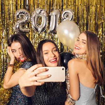 Tre amici che prendono selfie sulla celebrazione del nuovo anno