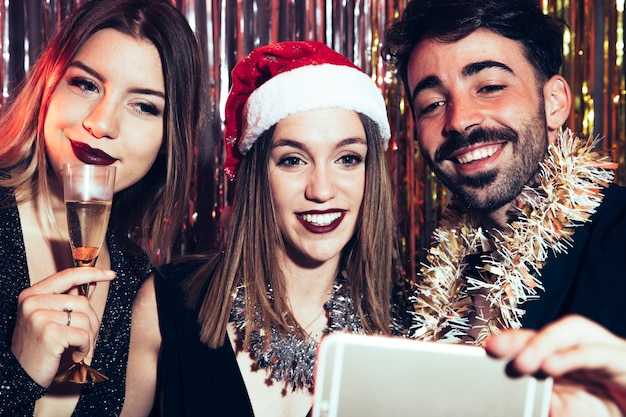 Tre amici che prendono selfie per il partito di nuovi anni