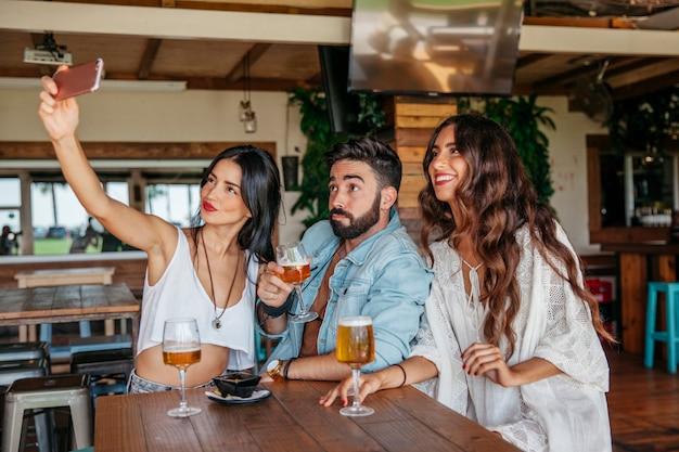 Tre amici che si prendono selfie con la birra