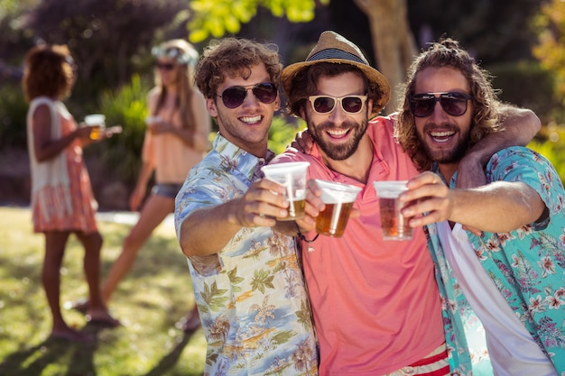 Three friends toasting glasses of beer