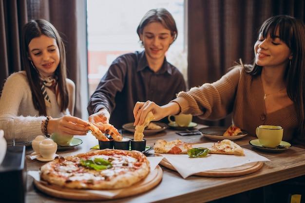 Tre amici insieme che mangiano pizza in un caffè
