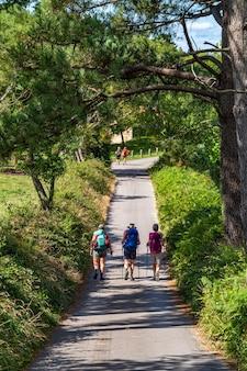 Трое друзей, идущих с рюкзаками, тропа, паломничество, путь святого джеймса, приключенческое путешествие, туризм, активный отдых, поход и концепция дружбы людей