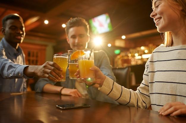 Трое друзей с алкогольными напитками веселятся за столиком в баре. группа людей отдыхает в пабе, ночной образ жизни, дружба, празднование события