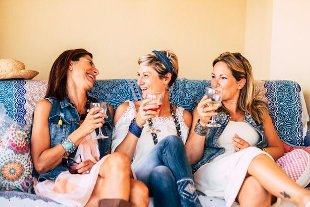3人の友人の女性が笑って、ソファに座って楽しんでいます