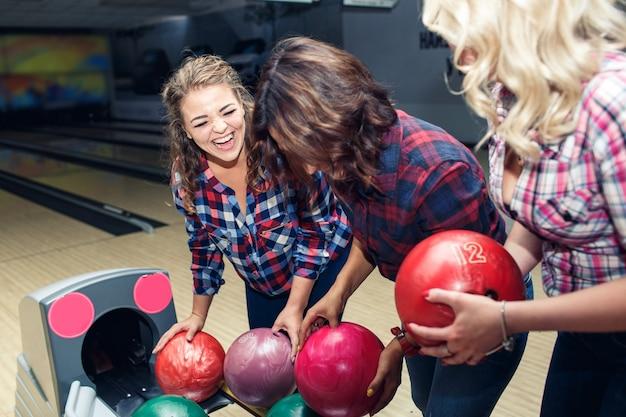 3人の面白い魅力的なガールフレンドがボウリングのボールを取る