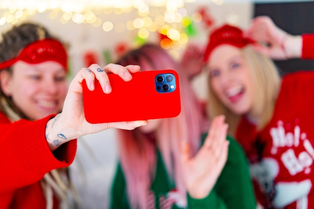 크리스마스 스웨터를 입은 세 명의 재미있는 소녀가 셀카를 찍습니다. 고품질 사진 프리미엄 사진