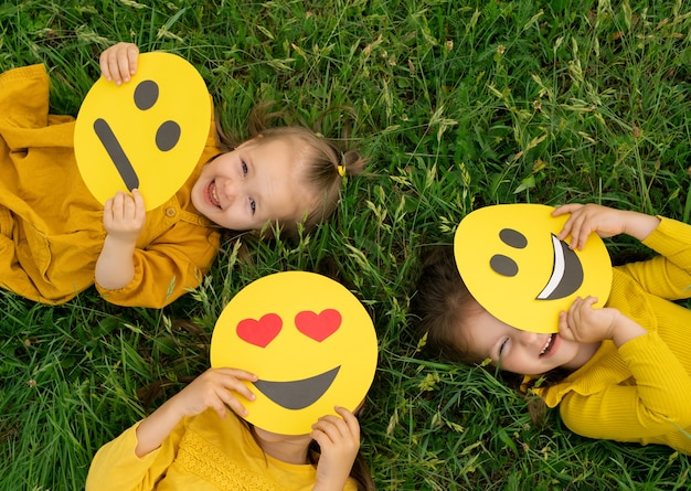 세 명의 재미있는 행복한 소녀들이 이모티콘 뒤에서 숨어서 밖을 내다본다