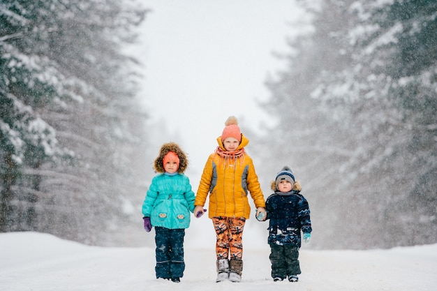 Three funny little children holding hands and standing on road near wood in winter stormy snowy weather. two girls with boy outdoor nature portrait on abstract background.  caution - kids on road