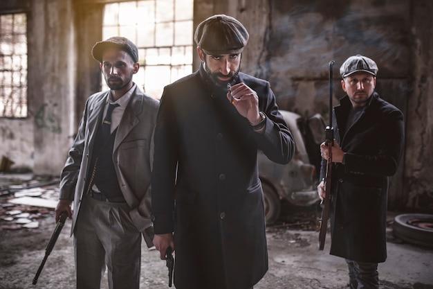 Трое бандитов с огнестрельным оружием и опасными в руках. мужчины в винтажной одежде и с оружием. заброшенный завод фон.