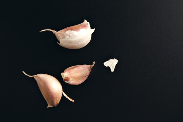 Three garlic cloves and some dry peel on a smooth black background