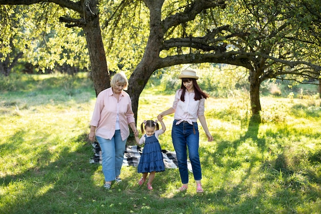 Three generation family, pleasan senior lady, young mom and little cute three years old girl, walking outside in the nature green park, holding hands and smiling.