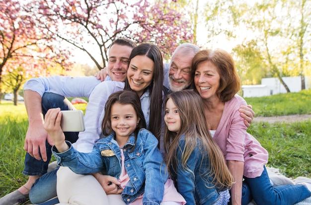 Семья из трех поколений со смартфоном сидит на улице в весенней природе и делает селфи.
