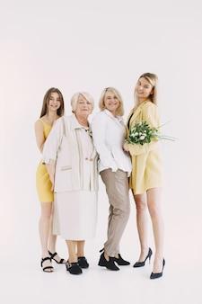 カメラを見て、灰色で隔離の抱擁の笑顔の女性の3世代