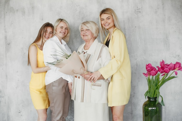 Three generation of smiling women looking at camera and hugging isolated on grey