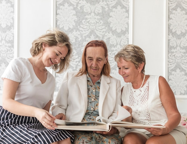 Three generation women looking photo album while sitting on sofa