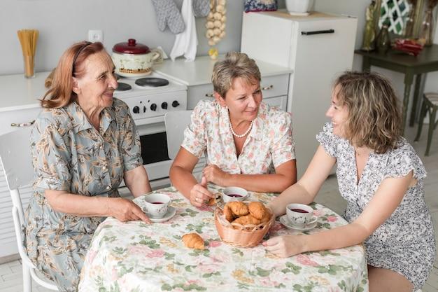 朝食中に何かを話している3世代の女性