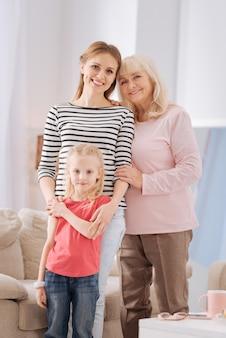 Три поколения. хорошая счастливая позитивная семья, стоящая вместе и смотрящая на вас, показывая свое единство