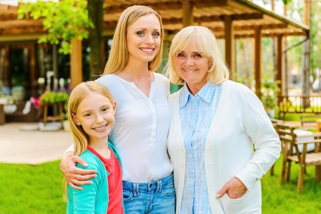 3대에 걸친 행복한 여성들. 집 앞에 서서 웃고 있는 3대 가족 여성