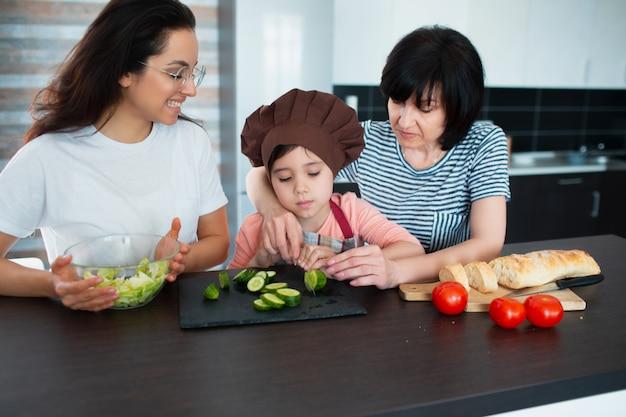 Три поколения женщин готовят на кухне. бабушка, мама и внучка проводят время вместе дома.