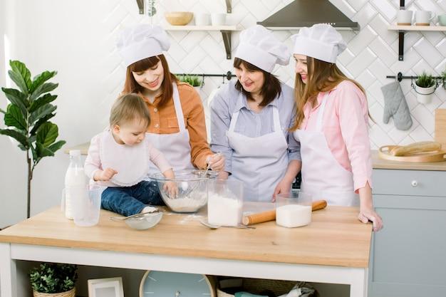Три поколения женщин в белых фартуках играют и смеются, замешивая тесто на кухне, смешивая муку с яйцами и готовя тесто на современной кухне
