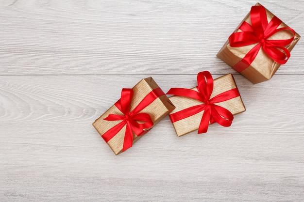 灰色の木製の背景に赤いリボンで結ばれた3つのギフトボックス。贈り物をするという概念。コピースペースのある上面図。