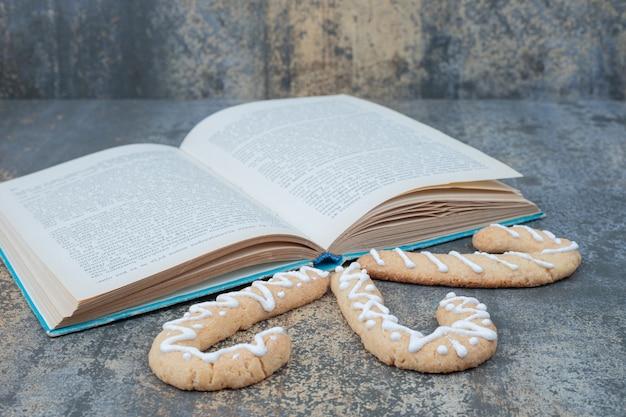 大理石の背景に3つのジンジャーブレッドクッキーと開いた本。高品質の写真