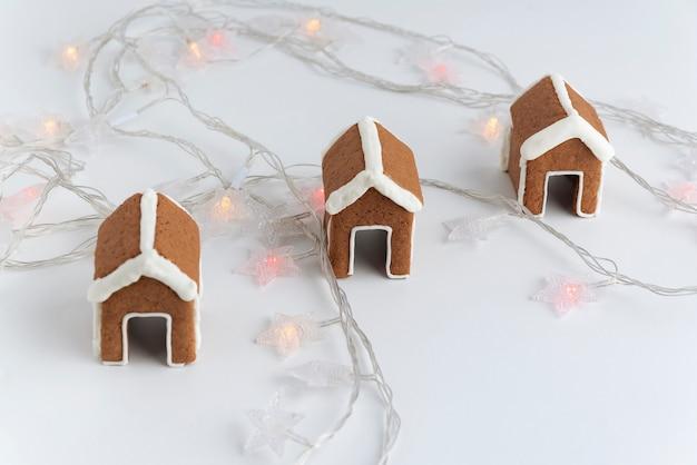 花輪の横にある白い背景の上のカップのための3つのジンジャーブレッドハウス。クリスマスの焼き菓子。