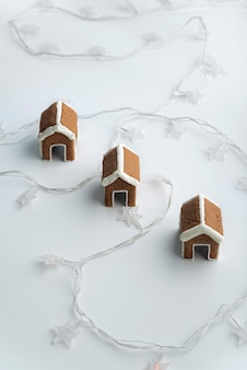 花輪と白い背景の上のカップのための3つのジンジャーブレッドハウス。クリスマスの焼き菓子。
