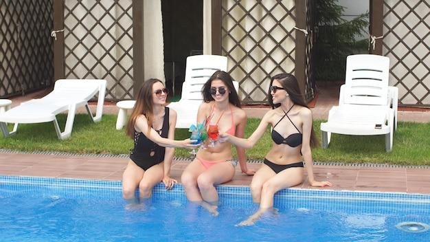 独身パーティーを祝うためにプールで会った3人のガールフレンド。カクテルを飲んで楽しんでください。