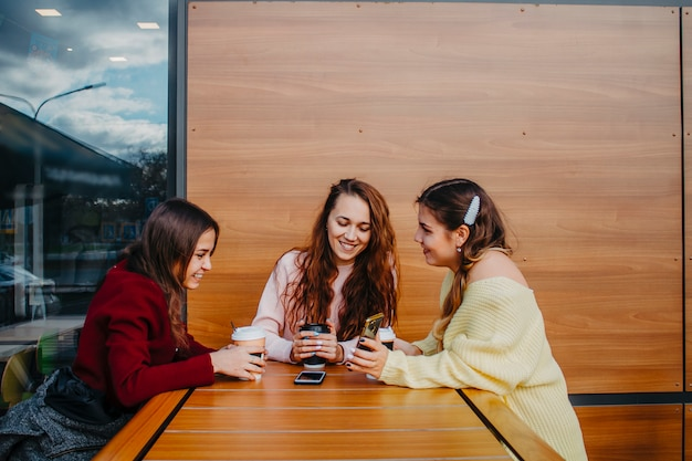 Three girlfriends are sitting in a cafe at a table, drinking coffee and talking.