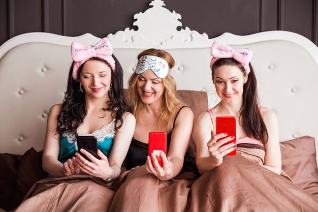 Три подружки устраивают пижамную вечеринку на шикарной кровати. девушки сидят на кровати, смотрят в телефон и улыбаются.
