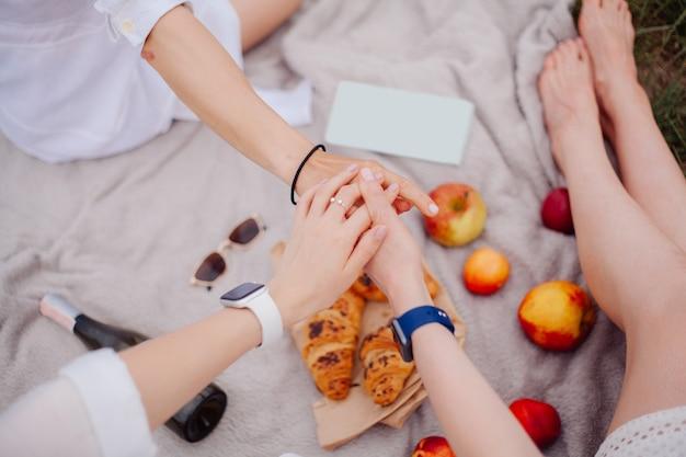 団結のしるしとして手をつないでピクニックにいる3人のガールフレンド