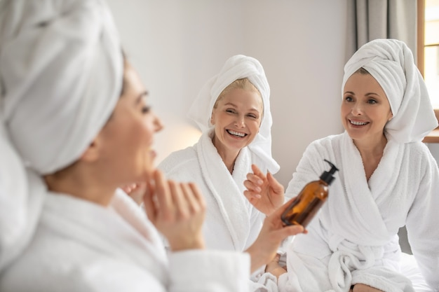 Three girlfriends with pleasure trying new cosmetic product