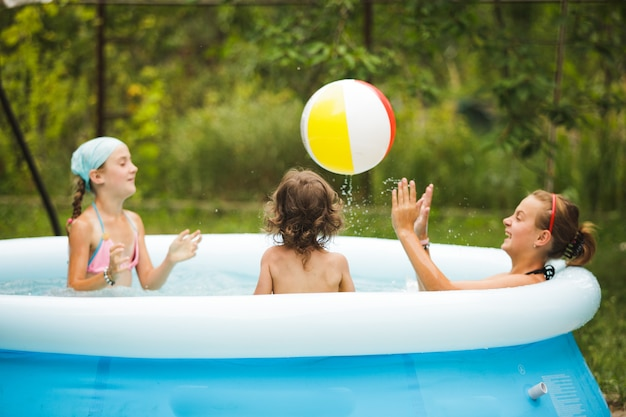 Three girls are swimming in the blue pool and playing with ball