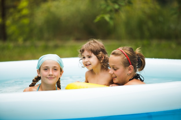 Three girls are swimming in the blue pool