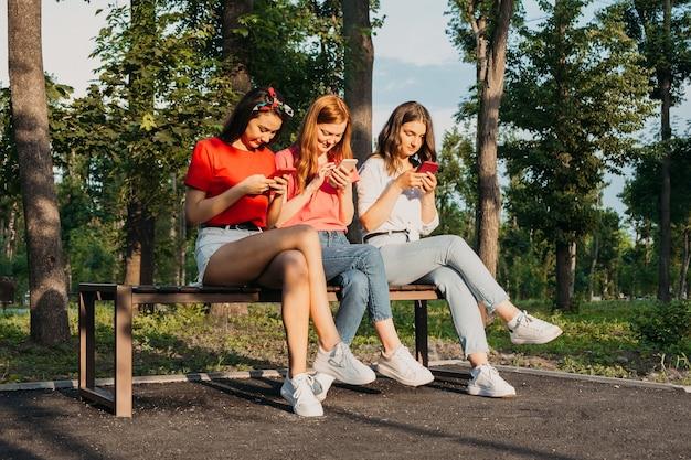 가제트를 사용하여 공원 gen z 어린 여자 친구에서 스마트폰으로 채팅하는 세 소녀와