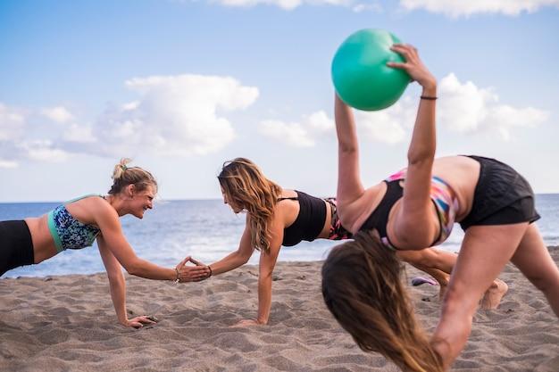 수평선과 푸른 바다와 해변에서 건강 피트니스 필라테스 운동을하는 세 여자. 야외 레저 활동을 즐기십시오. 하나는 공으로, 다른 하나는 하이파이 브로 밀기