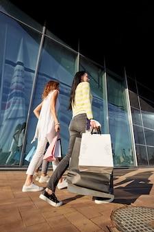 スタイリッシュなカジュアルな服を着た3人の女の子が買い物袋を持ってモールを歩きます