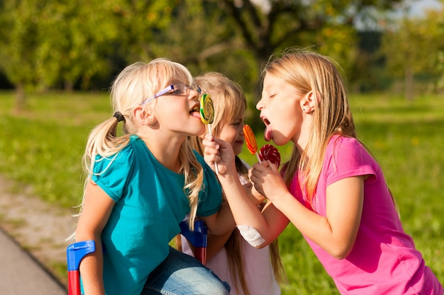 Three girls eating lollypops