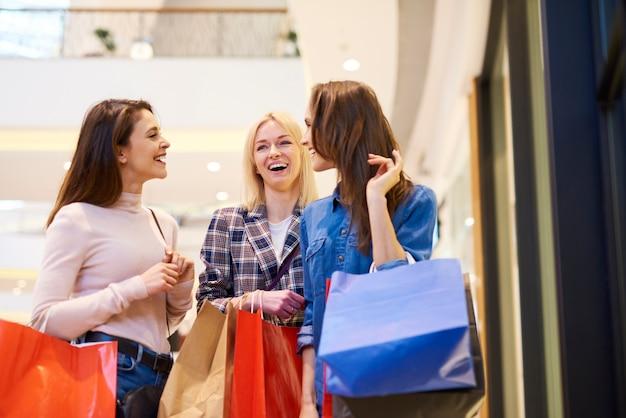Три девушки наслаждаются покупками в торговом центре
