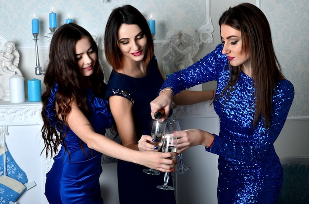 Three girls fill the glass of champagne