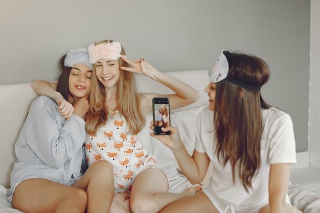 Three girls have a pajamas party at home