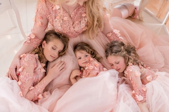 Three girls in pink dresses sleep on mom's knees