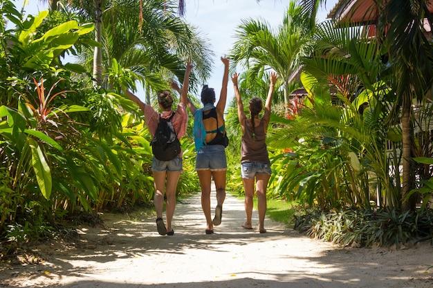 砂の小道を通って空中に手を置いてビーチに向かって歩いているショートパンツの3人の女の子