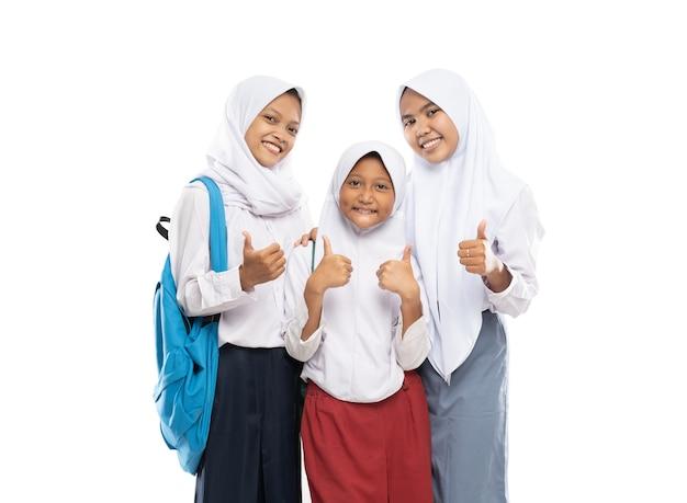 교복을 입은 베일을 입은 세 소녀가 배낭을 들고 엄지 손가락으로 서 있습니다.