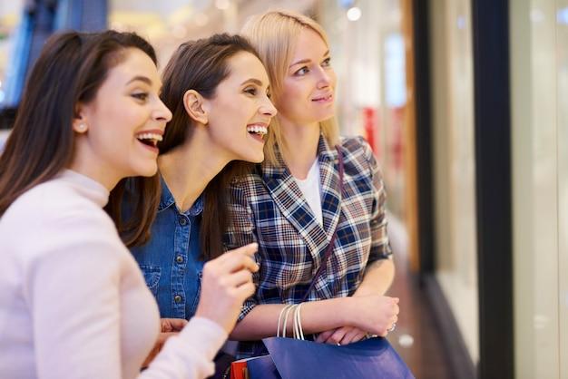 大きなウィンドウディスプレイを見ている3人の女の子